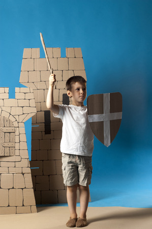 photo of the child on the medieval  castle decorations background made of cardboards