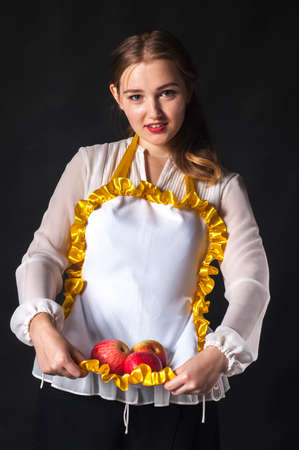 stereotypical: Photo of young housewife with apples in apron