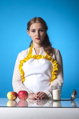 homemaker: Photo of serious homemaker in kitchen on blue background.