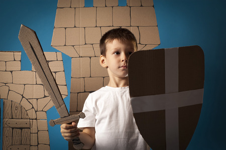 warder: photo of the child on the medieval  castle decorations background made of cardboards