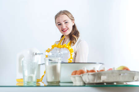 homemaker: Photo of young smiling homemaker in kitchen. Focus on homemaker. Front objects are in blur. Stock Photo