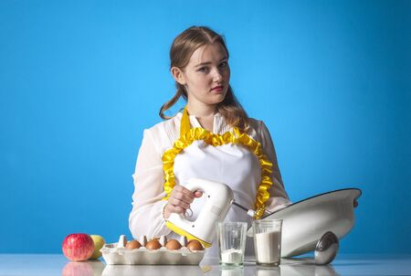 homemaker: Photo of  homemaker with mixer on blue background