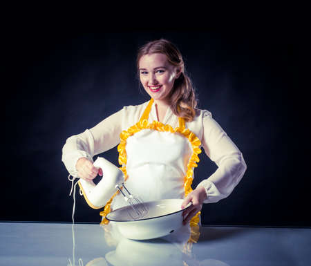 homemaker: Photo of young smiling homemaker with mixer and bowl