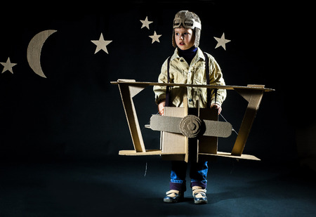 Boy is playing with handmade toy plane. Background – decorations of night sky photo