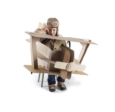 salutes: Boy in a pilots costume salutes. The action takes place near the cardboard airplane. Stock Photo