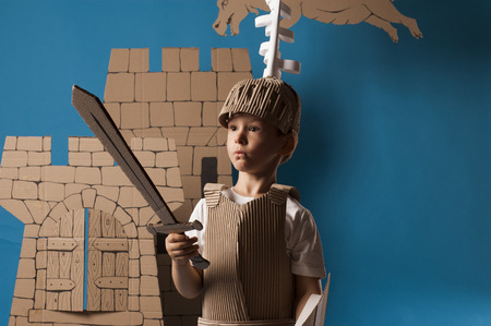 panicked: photo of the boy in medieval knight costume made of cardboards