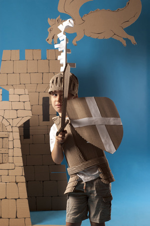 scared child knight is looking from the shield Stock Photo