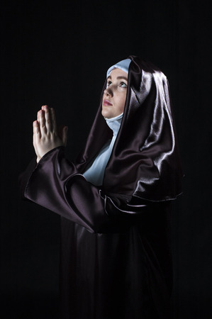 black nun: Young catholic nun with pray. Photo on black background. Low key lighting.