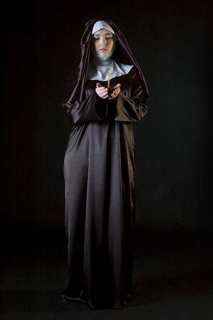 black nun: Young attractive catholic nun holding candle. Photo on black background. Stock Photo