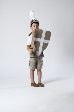 panicked: scared child knight is looking from the shield Stock Photo