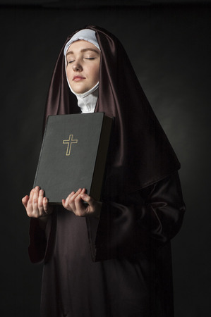 black nun: portrait of young woman nun holding bible over black background. Stock Photo