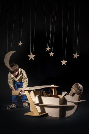 airscrew: Young aviator assembling corrugated plane on the dark night sky background Stock Photo