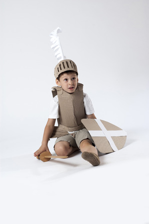 photo of the boy in medieval knight costume made of cardboards photo