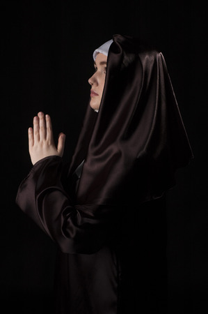 side lighting: Young attractive nun is praying. Side view.  Photo on black background. Low key lighting.