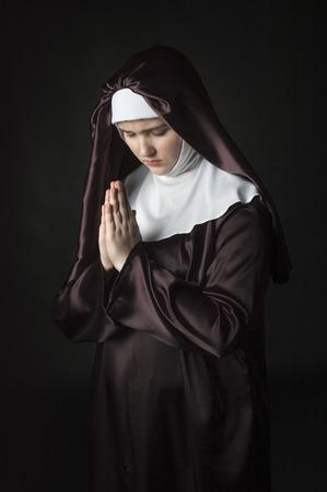 black nun: Young catholic nun with pray. Photo on black background. Stock Photo