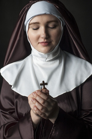 black nun: Young catholic nun holding cross in her hands. Focus on face. Cross and hands is blurred. Photo on black background. Stock Photo