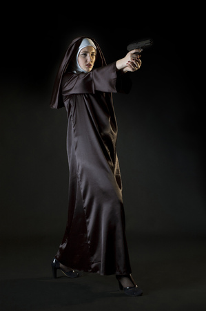 dynamic growth: Young nun shooting from gun. Low key photo on black background. Dynamic full growth photo. Stock Photo