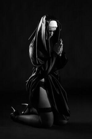 nun: Sexy nun sitting exposing her leg in black hoses.
