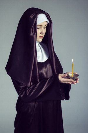 nun: Young catholic nun is holding candle in her hands. Photo on gray background. Stock Photo