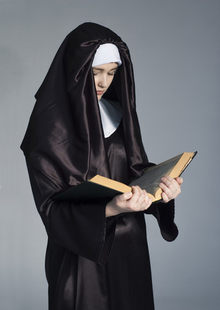 pious: Young beautiful woman nun reading bible on gray background.