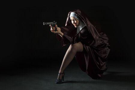 black nun: Nun shooting from gun sitting on her knees. Low key photo on black background. Stock Photo