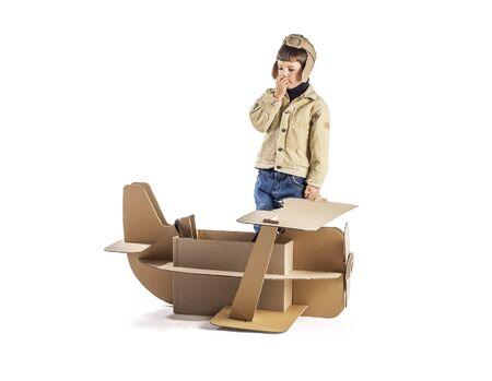 Boy thinking near cardboard plane. On white background.