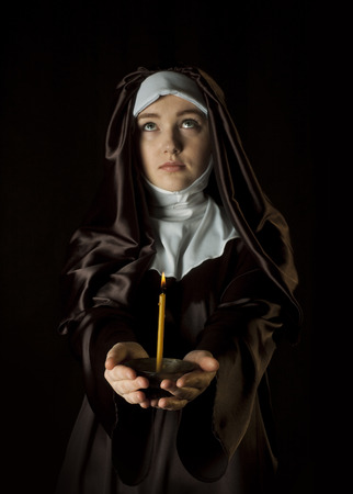 black nun: Young catholic nun is holding candle in her hands. Focus on candle. Face is blurred. Photo on black background.