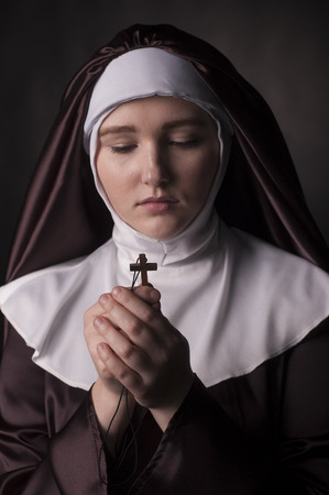 black nun: Young catholic nun holding cross in her hands. Photo on black background. Stock Photo