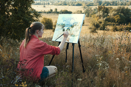 Young girl-artist is painting with watercolor on the plein Air