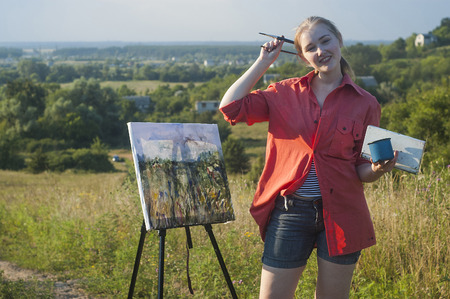 plein: Young girlartist is painting with watercolor on the plein Air. Rural landscape is on the background.