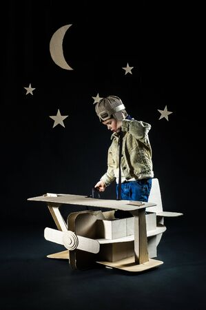 Boy is playing with handmade toy plane. Decorations of night sky is on background. photo