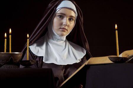 black nun: Young beautiful woman nun reading bible on black  background. Through the candles. Low-key lighting.