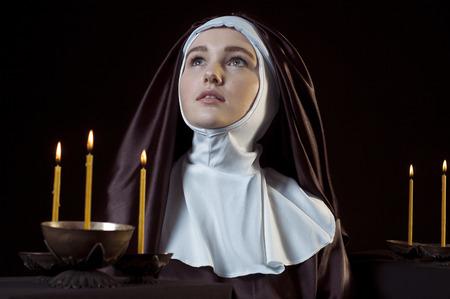 black nun: Young catholic nun through the candles. Photo on black background. Low key lighting.