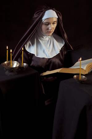 virgin girl: Young beautiful woman nun reading bible on black  background. Through the candles.