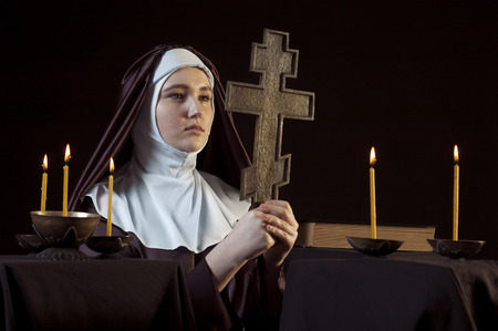 black nun: Young catholic nun is praying. Orthodox cross in her hands. Photo on black background. Stock Photo