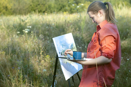 plein: Young girl-artist is painting with watercolor on the plein air