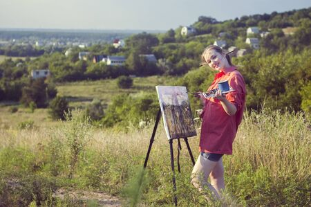 plein: Young girl-artist is painting with watercolor on the plein Air. Rural landscape is on the background. Stock Photo