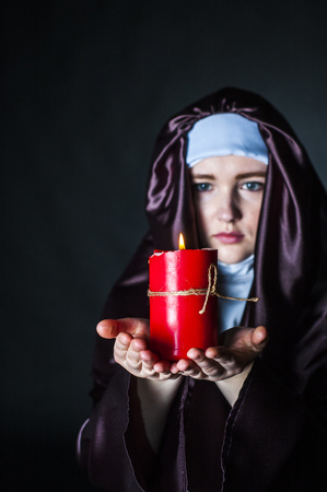 black nun: Young catholic nun is holding candle in her hands. Focus on candle. Photo on black background. Stock Photo