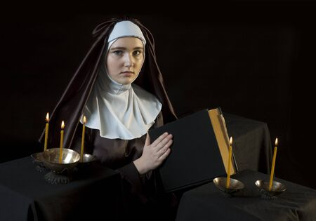 low key lighting: Young catholic nun through the candles. Photo on black background. Low key lighting.