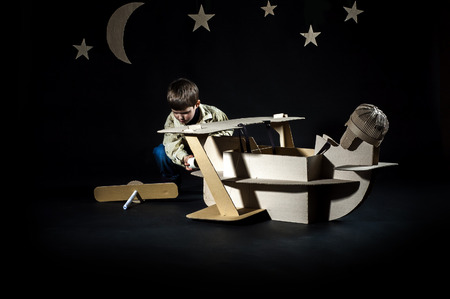 airscrew: Young aviator assembling corrugated plane on the dark night sky background.