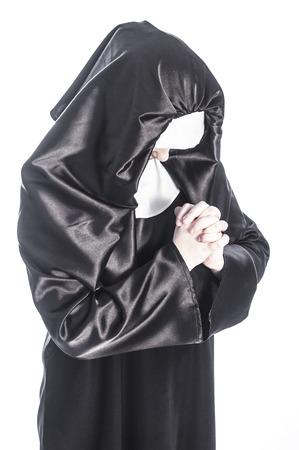 religious habit: Young nun prays. Photo on white background.