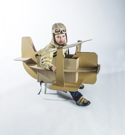Boy in a pilots costume salutes. The action takes place near the cardboard airplane. Stock Photo