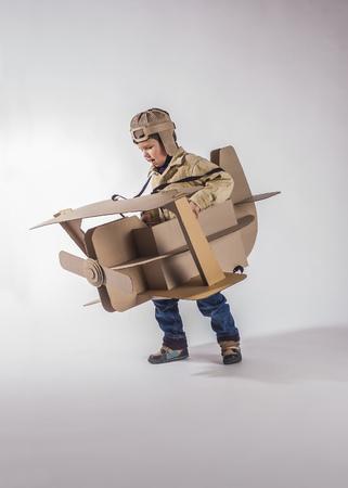 Young aviator in a homemade cardboard biplane. On gray background. Zdjęcie Seryjne