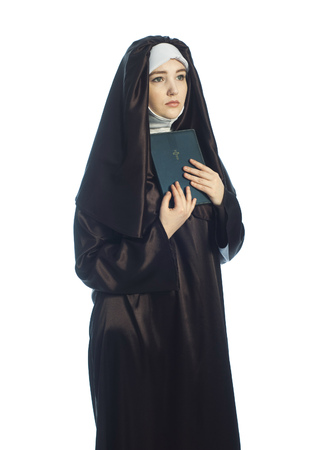 pious: portrait of young woman nun holding bible over white background.