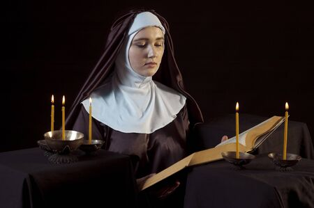 lowkey: Young beautiful woman nun reading bible on black  background. Through the candles. Low-key lighting.