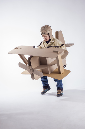 aviator: Young aviator in a homemade cardboard aircraft on white background. Stock Photo