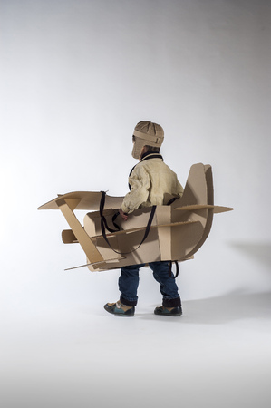 flight helmet: Child is flying away on hand made cardboard plane. Back view.