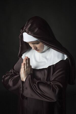 nun: Young nun prays. Photo on black background. Low key lighting.