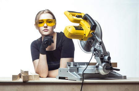 miter: young beautiful woman in overalls and glasses with disk saw preparing for cutting. Photo on white background.