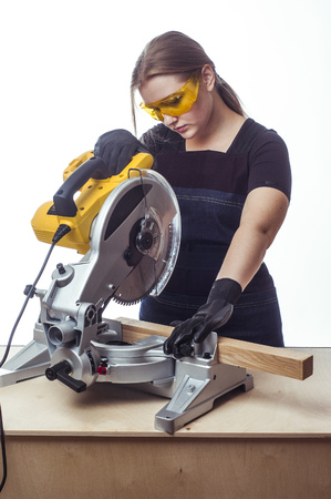 young worker: young beautiful woman in overalls and glasses with disk saw preparing for cutting. Photo on white background.
